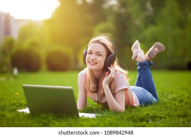 Girl in the Park working on a laptop with headphones