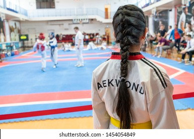 the girl participates in Taekwondo competitions in a sports kimono on the background of Taekwondo competitions close-up
