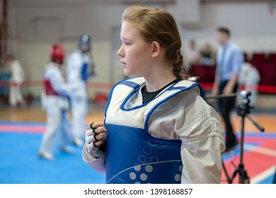a girl participating in Taekwondo competitions in a blue protective vest on the background of Taekwondo competitions close-up