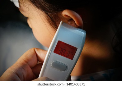 Girl and patch for fever reduction And fever meter Thermometer. She has a high fever.