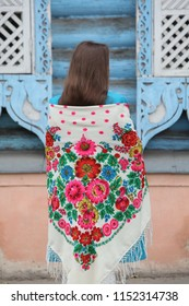 Girl in Pavlovo Posad shawl with Petrykivka painting and wooden blue house in Moscow city (Russia)