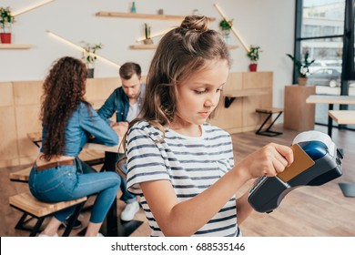 girl paying with EDC machine while her parents sitting on background