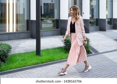 a girl in a peach jacket, a plush skirt and sneakers is walking along a stone street with a great mood. On the territory of a modern residential complex.