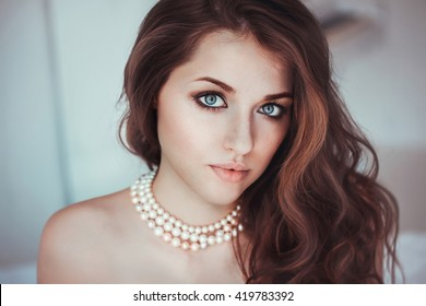 Girl with a pearl necklace close-up portrait bare shoulders