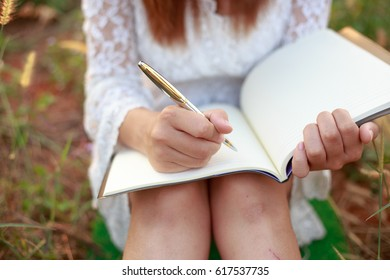 girl with pen writing on notebook on grass.