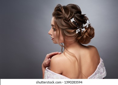 girl with perfect curly volume looking sideways and touching her shoulder