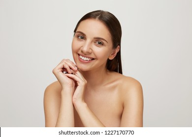 Girl with perfect healthy fresh skin looks camera as in the mirror, smiling, palms folded under the chin, very glad and satisfied with result, head and naked shoulders, over white background
