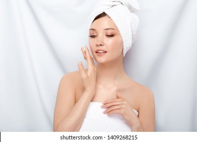 girl with perfect skin in bath towel applying facial cream and looking down, preety female after spa putting on moisturizer