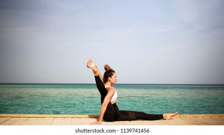 girl performs asana yoga against the beautiful sea