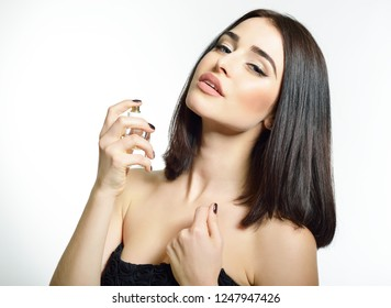 Girl with perfume, young beautiful woman holding bottle of perfume and smelling aroma. Pretty lady posing with a bottle of expensive perfume.