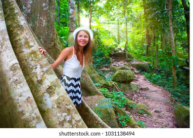 girl person tourist smile and peeks out from huge high thousand year old tropical tree with large big long roots. Tropical forest, exotic tour adventure ancient dinosaurs era concept Thailand Bodhi