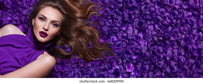 The girl in the petals. Beautiful young girl lies in the violet petals in a long dress. Glamor. Hair - curls. Makeup - arrows, purple lipstick. Love, romance.