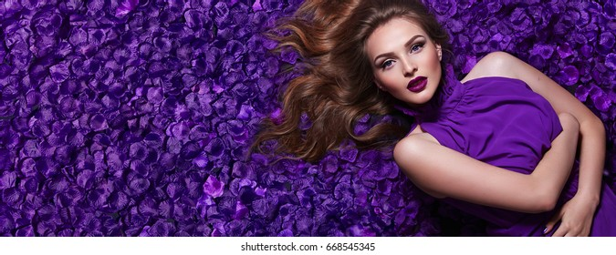 The girl in the petals. Beautiful young girl lies in the violet petals in a long dress. Glamor, luxe. Hair - curls. Makeup - arrows, purple lipstick. Love, romance.