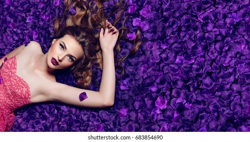 The girl in the petals. Beautiful young girl lies in the violet petals in a long dress.  Glamor.. Hair - curls. Makeup - arrows, purple lipstick. Love, romance.