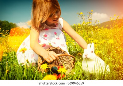 Girl petting Easter bunny on meadow with eggs - filtered image