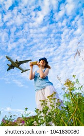 girl with a phone on the background of a flying airplane