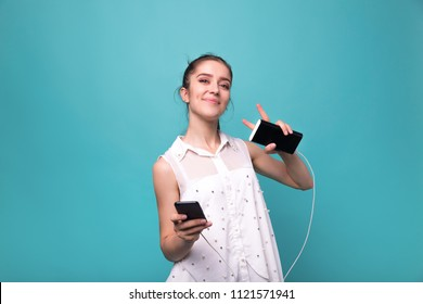 Girl with phone and power bank in hands Young beautiful woman smiles with a phone and charging in his hand blue cyan background Studio