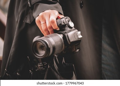 A girl photographer in a black raincoat in rainy weather holds a black umbrella and a SLR camera in her hand.