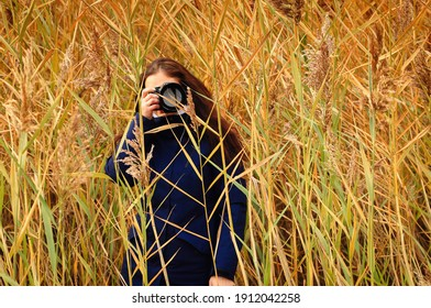 A girl photographer in a blue jacket, photographing the autumn nature through the grass.