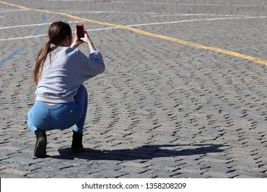 Girl photographer in jeans taking pictures on smartphone squatting on the street. Shadow on pavement, woman tourist, female fashion