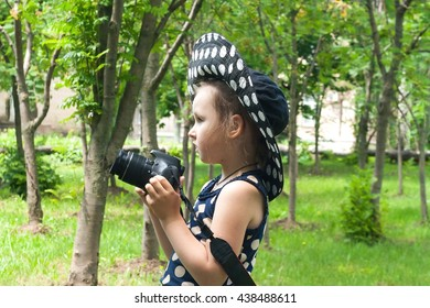 Girl photographer . To look in a lens . Happy childhood . beautiful childhood .  the advanced child . The girl in a hat from the sun. A hat in peas. Settings of a camera