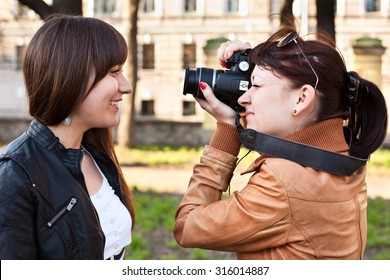 The girl photographer photographing the model in outdoors