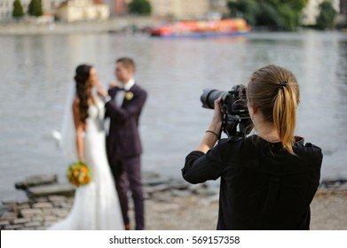 The girl photographer photographing a wedding in Prague against the background of the river