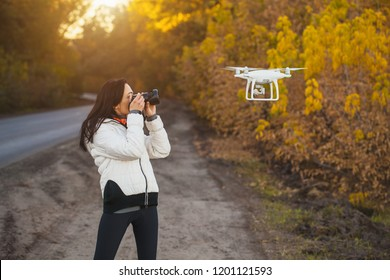 girl photographer shoots a flying drone in the autumn park