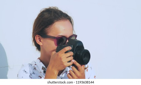 The girl photographer shoots the model in the open air, close-up, the lens of the camera.