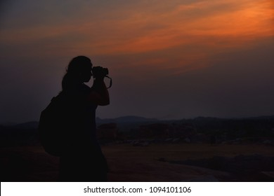 Girl photographer taking the picture of sunset