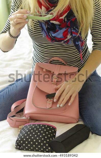 Girl photographing her bag and makeup