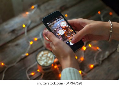 girl photographing on phone with coffee mugs and illuminations