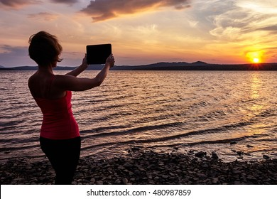 Girl photographing the sunset on the table, summer