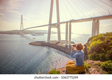 Girl photographs the cruise liner passing under Russky Bridge on the smartphone