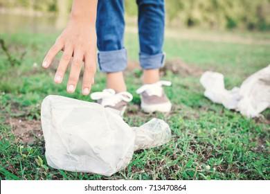 Girl picking garbage in park ,volunteer concept