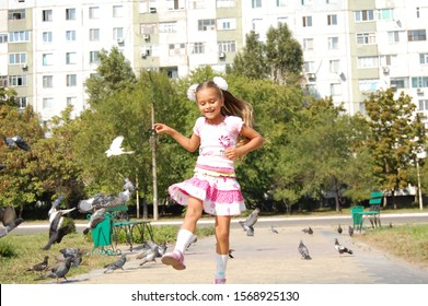 Girl and pigeons. A girl runs along the alley and scatters pigeons. Birds take off. Little girl chases pigeons in the park