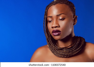 Girl with pigtails. A girl from Africa. African girl looking down.