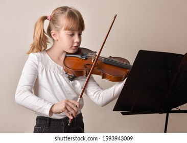Girl with pigtails playing the violin looking at the score on a music stand. Horizontal composition. Front view.