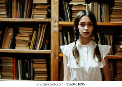 Girl with pigtails in white blouse at old library.