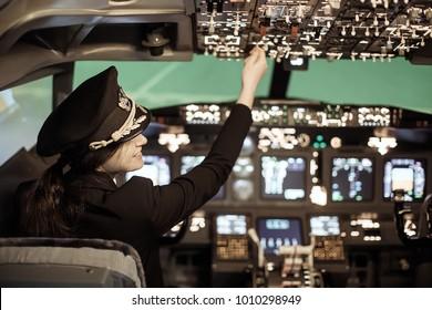 Girl pilot in uniform flying light craft plane in the sky