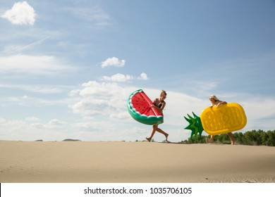 Girl with pineapple floatie chasese girl with watermelon floatie on sand dune