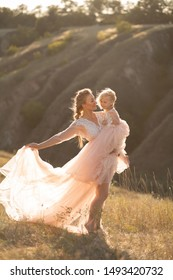 A girl in a pink airy dress holds a little girl in her arms. Sunset, summer. Field and hills.