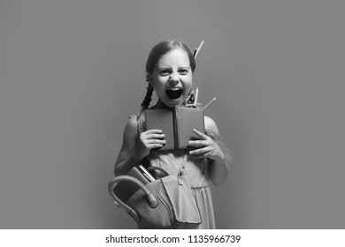 Girl with pink bag holds open blue notebook. Back to school and childhood concept. Pupil with long braids, isolated on blue background. Kid with happy screaming face and colored pencils in hair