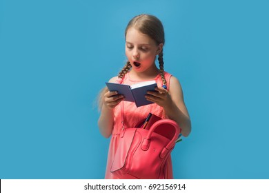 Girl with pink bag reads blue book. Back to school and childhood concept. Pupil with braids, isolated on blue background. Kid with surprised face expression and stylish outfit