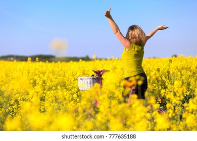 girl with pink bike in the field of yellow rape standing with hands up in wonder