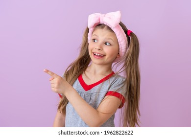 A girl with a pink bow on her head points to the side.