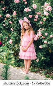 girl in a pink dress with a bow on her head in the rose garden. Girl doll.