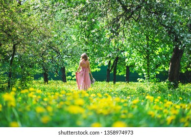 Girl in pink dress bright summer lawn with yellow flowers high fresh green grass is a magical place for picnic. Rest on the nature on a hot summer day. Soft focus and beautiful bokeh.
