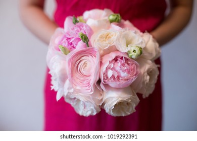 A girl in a pink dress is holding lovely bridal bouquet of pink peonies Sarah Bernhardt, ranunculuses Hanoi, Keira roses and white Eustoma on the window background. Wedding floristry