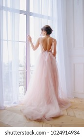 Girl in a pink dress near the window